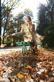 Autumn woman happy. Beautiful woman in autumn scenery on a park bench Stock Photos