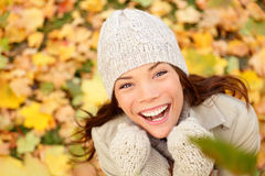 Autumn woman happy with colorful fall leaves. In beautiful yellow forest foliage. Excited cheerful girl looking at camera joyful with beautiful autumn colors Stock Photo