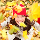 Autumn woman happy with colorful fall leaves. Falling in forest foliage. Excited cheerful girl looking at camera joyful with beautiful autumn colors Royalty Free Stock Images