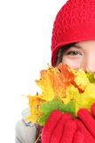 Autumn woman happy with colorful fall leaves. Isolated on white background in studio. Cheerful girl hiding behind autumn leaves. Portrait close up of Stock Image