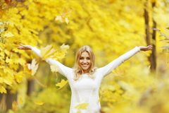 Autumn woman. Happy woman drop up leaves in autumn park Stock Photo