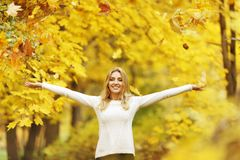 Autumn woman. Happy woman drop up leaves in autumn park Stock Images