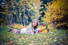 Autumn woman happy in fall park lays at basket having fun smiling in beautiful colorful forest foliage Royalty Free Stock Images