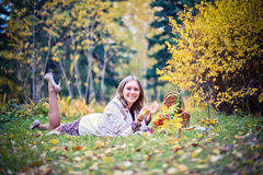 Autumn woman happy in fall park lays at basket having fun smiling in beautiful colorful forest foliage Royalty Free Stock Photos