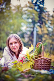 Autumn woman happy in fall park lays at basket having fun smiling in beautiful colorful forest foliage Stock Photography