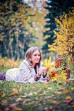 Autumn woman happy in fall park lays at basket having fun smiling in beautiful colorful forest foliage Stock Images