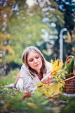 Autumn woman happy in fall park lays at basket having fun smiling in beautiful colorful forest foliage Stock Photo