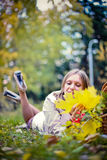 Autumn woman happy in fall park lays at basket having fun smiling in beautiful colorful forest foliage Royalty Free Stock Photography
