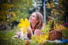 Autumn woman happy in fall park lays at basket having fun smiling in beautiful colorful forest foliage Stock Image