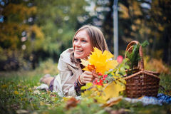 Autumn woman happy in fall park lays at basket having fun smiling in beautiful colorful forest foliage Stock Photos