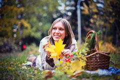 Autumn woman happy in fall park lays at basket having fun smiling in beautiful colorful forest foliage Royalty Free Stock Photo