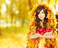 Autumn Woman holding Apples, Fashion Model in Yellow Fall Leaves Stock Image
