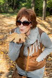 Autumn woman holding big brown leaf Stock Photo