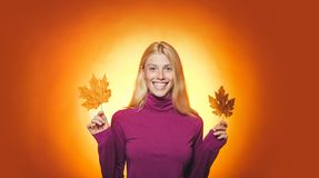 Autumn woman holding gold leaf. Attractive young woman wearing in fashionable seasonal clothes having Autumnal mood stock images