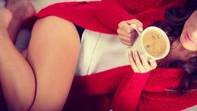 Autumn woman holds mug with coffee sitting on sofa Royalty Free Stock Photo