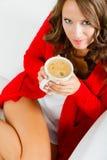 Autumn woman holds mug with coffee sitting on sofa Royalty Free Stock Image