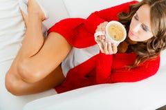 Autumn woman holds mug with coffee sitting on sofa Stock Photography