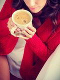 Autumn woman holds mug with coffee sitting on sofa Stock Images