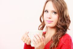 Autumn woman holds mug with coffee warm beverage. Attractive fall girl long hair red autumnal sweater holding white mug with coffee warm beverage. Woman warming Royalty Free Stock Images