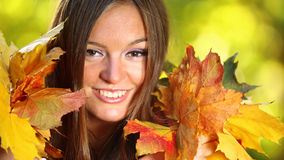 Autumn woman on leafs background. Young woman with autumn leaves in hand and fall yellow maple garden background stock images