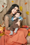 Autumn woman with little boy on yellow fall leaves, apples, pumpkin and decoration on textile, happy family and country concept Stock Photo