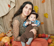 Autumn woman with little boy on yellow fall leaves, apples, pumpkin and decoration on textile, happy family and country concept Royalty Free Stock Image