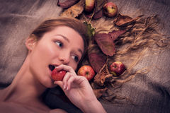 Autumn woman lying on the canvas with fall leaves and fruits in her hair, biting an apple Royalty Free Stock Photography