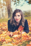 Autumn Woman Lying on Fall Leaves Stock Photography
