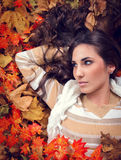 Autumn woman lying in orange leaves. Young woman in autumn orange leaves, outdoor royalty free stock photography