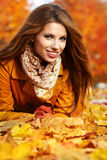 Autumn woman lying over leaves and smiling Royalty Free Stock Images