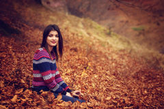 Autumn woman lying over leaves and smiling Stock Photos