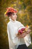 Autumn Woman. Mooie creatieve make-up en haarstijl in openluchtspruit. Meisje dat met bladeren in haar een mand met appelen houdt Stock Afbeelding