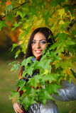 Autumn woman next to leaves Stock Images