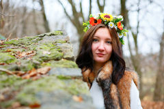 Autumn woman portrait with flowers wreath in fur coat near a stone wall Royalty Free Stock Image
