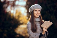 Retro Chic Girl with Beret Holding a Paper Wrapped Package royalty free stock photos