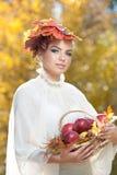 Autumn Woman. Schönes kreatives Make-up und Frisur Trieb im im Freien. Mädchen mit Blättern im Haar, das einen Korb mit Äpfeln häl Lizenzfreies Stockfoto