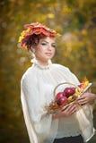 Autumn Woman. Schönes kreatives Make-up und Frisur Trieb im im Freien. Mädchen mit Blättern im Haar, das einen Korb mit Äpfeln häl Stockbild