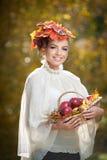 Autumn Woman. Schönes kreatives Make-up und Frisur Trieb im im Freien. Mädchen mit Blättern im Haar, das einen Korb mit Äpfeln häl Lizenzfreie Stockfotos