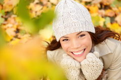 Autumn woman in yellow leaves portrait. Utumn portrait of happy lovely and beautiful mixed race Asian Caucasian young woman in forest in fall colors royalty free stock photo