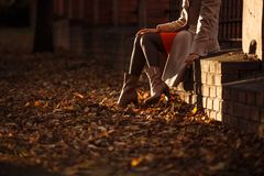 Autumn women`s boots kick fallen dry leaves. royalty free stock photo