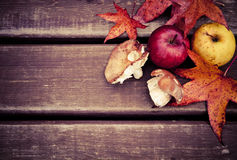 Autumn wooden background with mushrooms and apples Royalty Free Stock Photos
