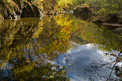 Autumn on woodsy river 2. The small woodsy river at autumn. In water are fallen leaves and reflection of trees and sky with clouds Royalty Free Stock Photo