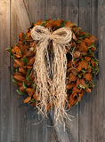 Autumn wreath. An Autumn colored wreath hangs on weathered barnwood royalty free stock photography