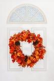 Autumn Wreath Hanging en la puerta blanca Imagen de archivo