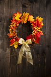 Autumn wreath. Hanging on a wooden door royalty free stock image