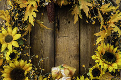Autumn Wreath. Of sunflowers and fall leaves on rustic wood background stock photo