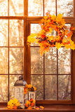 Autumn wreath at the sunset window background stock image