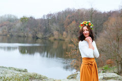 Autumn young beautiful woman with flower wreath outdoors near the pond Stock Photos