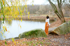 Autumn young girl near the pond Stock Photos