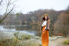 Autumn young woman with flower wreath in fur coat outdoors near the pond Royalty Free Stock Photography